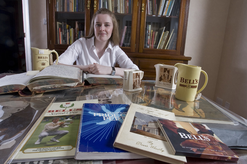 Alia Campbell, Assistant Archivist at Diageo, with items from the Bell's Scotch whisky collection in the research room. Image courtesy of Diageo Archives.