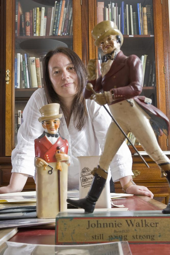 Christine McCafferty, Diageo Archive Manager, with items from the Johnnie Walker Scotch whisky collection in their research room. Image courtesy of Diageo Archives.