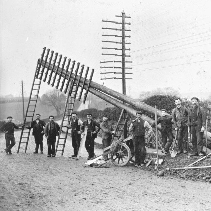 Engineering work gang erecting telegraph pole.